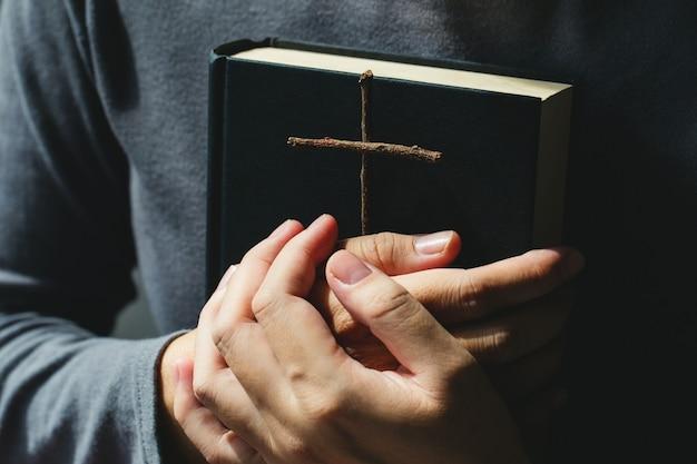 Vrouwen houden de bijbel en kruisen van zegen van god. vrouwen in religieuze concepten