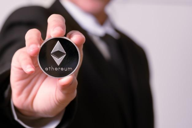 Vrouwen houden de cryptocurrency-munt bij de hand. fysieke bitcoins gouden en zilveren munten