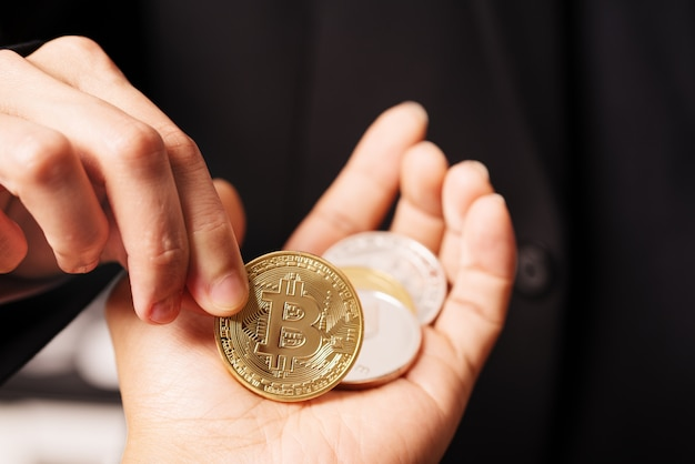 Vrouwen houden de cryptocurrency-munt bij de hand.