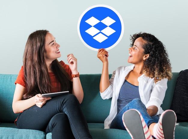 Vrouwen houden een dropbox-pictogram omhoog