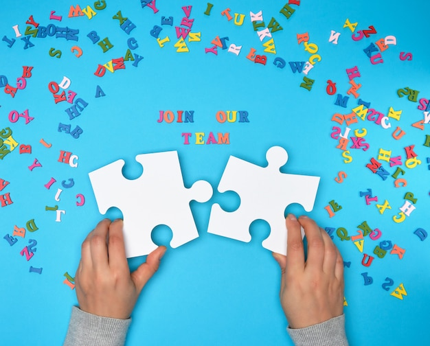 Vrouwen houden grote witte puzzels en de inscriptie wordt lid van ons team