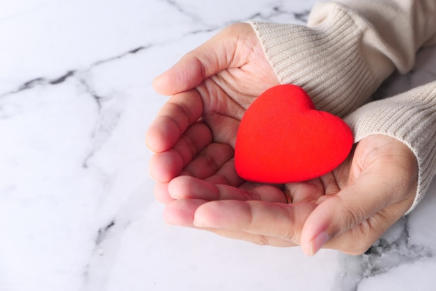 Vrouwen houden rood hart close-up.