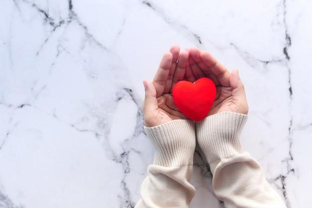 Vrouwen houden van rood hart op tegels achtergrond, bovenaanzicht,