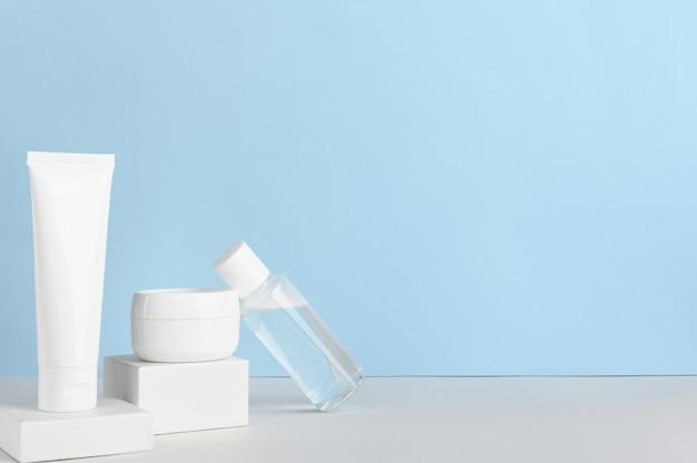 Vrouwen huidverzorgingsproducten lege pakketten samenstelling op blauwe achtergrond.