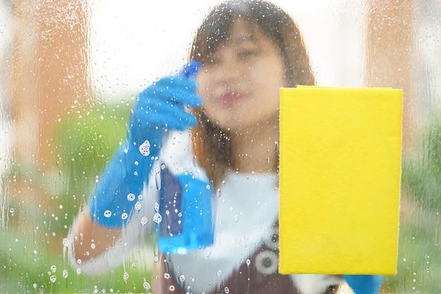 Vrouwen huishoudster die de spiegel met gele spons schoonmaken