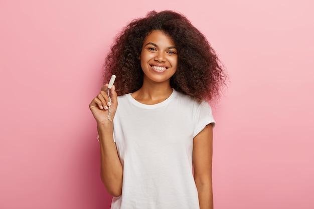 Vrouwen hygiëne bescherming concept. vrolijke donkere vrouw houdt katoenen tampon vast