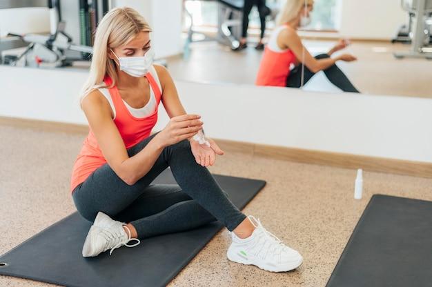 Vrouwen in de sportschool die haar handen desinfecteren
