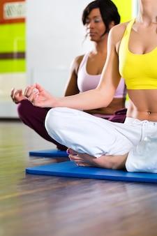 Vrouwen in de sportschool doen yoga oefening voor fitness