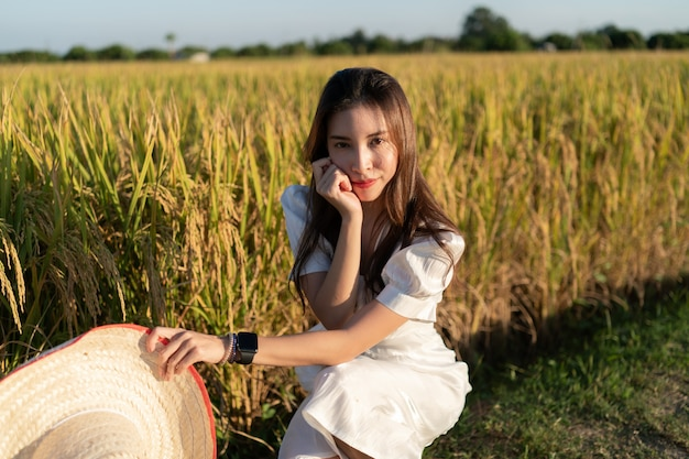 Vrouwen in de witte jurk genieten van natuurlijk in gouden rijstveld.