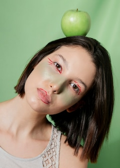 Vrouwen in evenwicht brengende appel op hoofd terwijl het overhellen