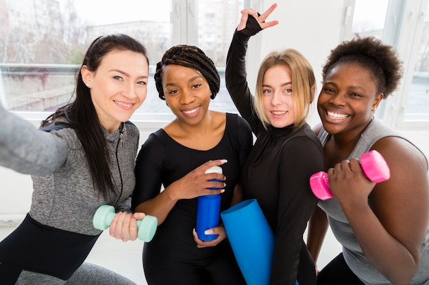 Vrouwen in fitnessles die selfies nemen