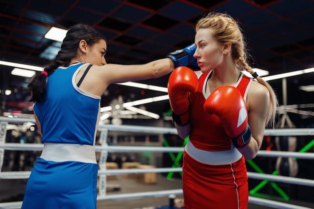 Vrouwen in handschoenen boksen op de ring, bokstraining. vrouwelijke boksers in de sportschool, kickboksen sparringpartners in sportclub, punch praktijk