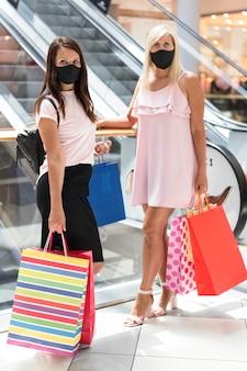 Vrouwen in het winkelcentrum die maskers dragen