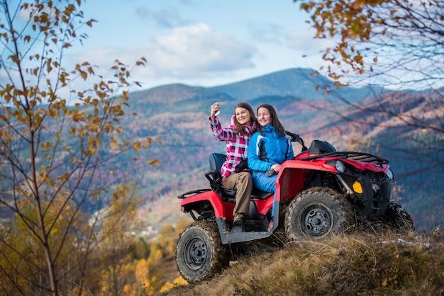 Vrouwen in jasjes op rode atv op de heuvel maakt selfie op de telefoon