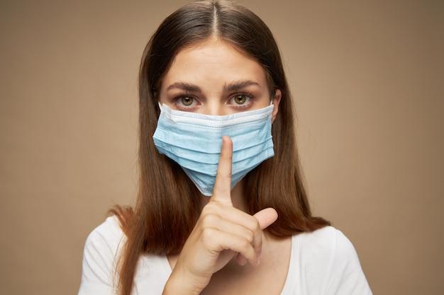 Vrouwen in medisch masker en wijsvinger zien er zelfverzekerd uit in beige ruimte