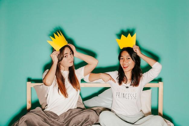 Vrouwen in papieren kronen op bed