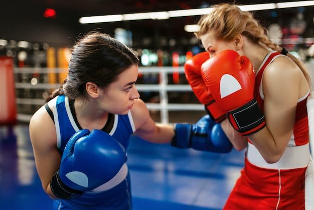 Vrouwen in rode en blauwe handschoenen die op de ring boksen