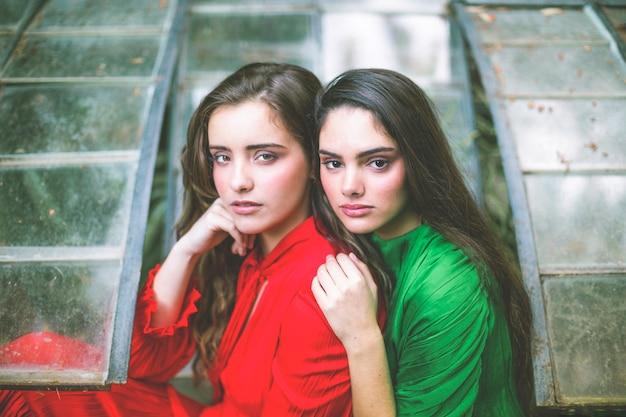 Vrouwen in rode en groene jurken kijken naar de camera