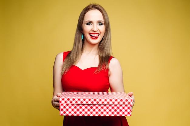 Vrouwen in rode en kleding die voor nieuw jaar glimlacht houdt.
