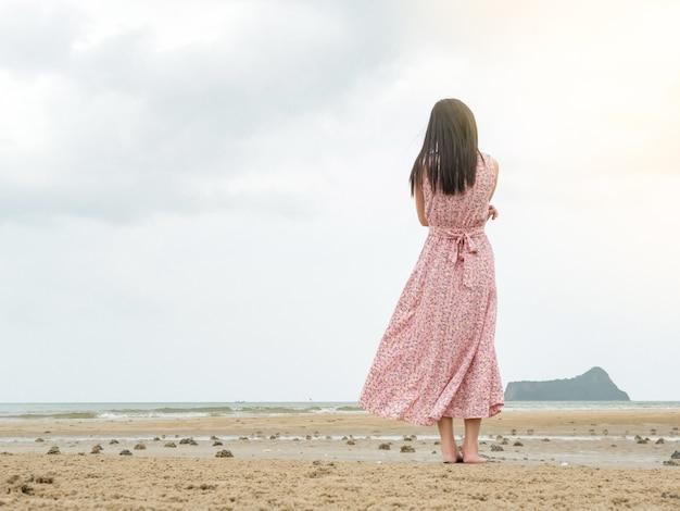 Vrouwen in roze jurken, staan alleen op het strand.