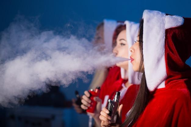 Vrouwen in santa claus kostuums roken elektronische sigaret op blauwe achtergrond