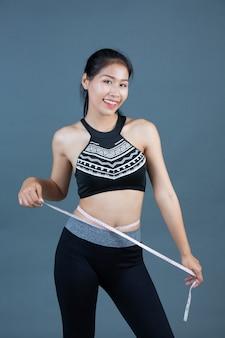 Vrouwen in sportkleding houden een taille lijn vast.