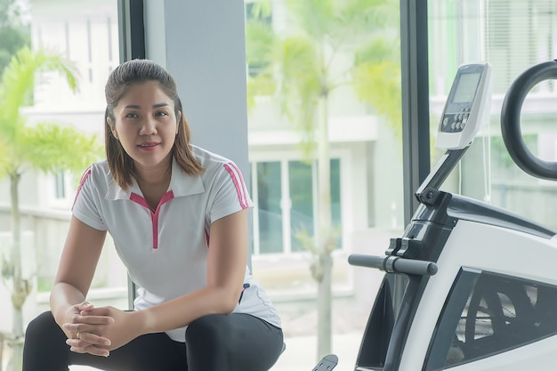 Vrouwen in sportkleding leunen achterover en ontspannen na een zware training.