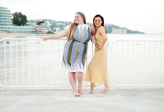 Vrouwen in vrijetijdskleding die op een lang afstandshek leunen l