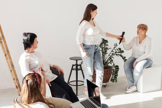 Vrouwen in witte shirts praten over de microfoon