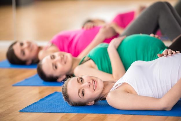 Vrouwen in yogales liggen op matten in een fitnessstudio.