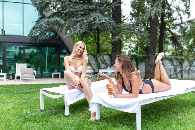 Vrouwen in zwemkleding zonnebaden bij het zwembad en cocktails drinken