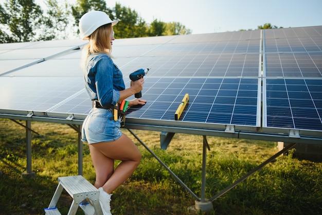 Vrouwen ingenieur bezig met het controleren van apparatuur bij groene energie zonne-energiecentrale