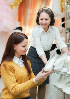 Vrouwen kiest witte schoenen in de winkel