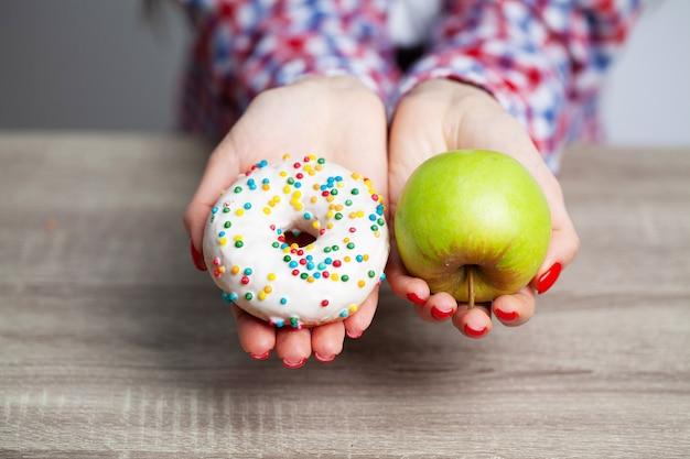 Vrouwen kiezen tijdens haar dieetsessie de keuze tussen donut en groene appel