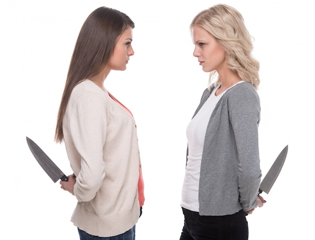 Vrouwen kijken elkaar aan en houden een mes vast.