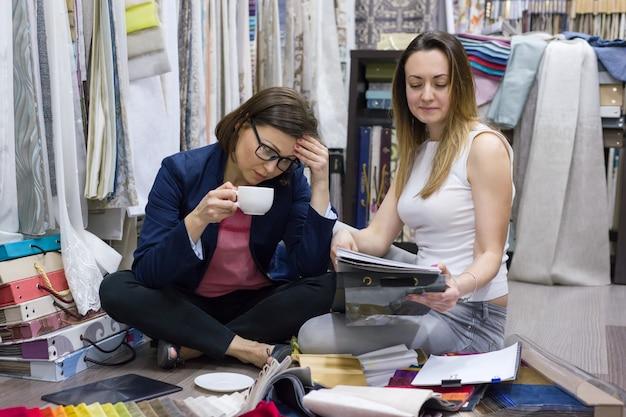 Vrouwen kijken monsters van stoffen voor gordijnen, meubels