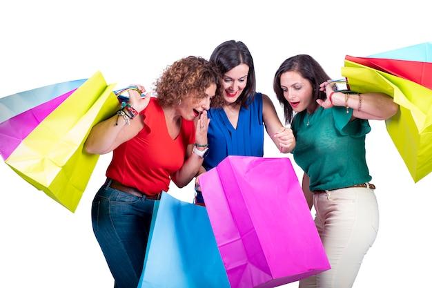 Vrouwen kijken naar het winkelen in de tassen en verrassen zichzelf op een witte achtergrond.