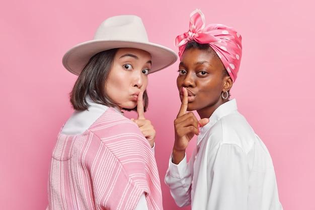 Vrouwen kijken stiekem naar de camera iets verbergen vragen om stil te zijn zwijgen gebaar maken stijlvolle kleding dragen poseren naast elkaar geïsoleerd op roze