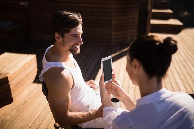 Vrouwen klikkende foto van de mens met mobiele telefoon