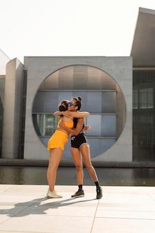 Vrouwen knuffelen buitenshuis full shot