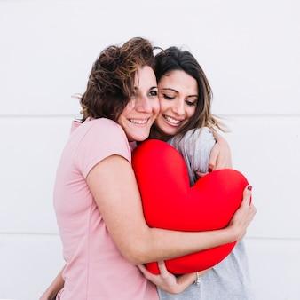 Vrouwen knuffelen met speelgoedhart