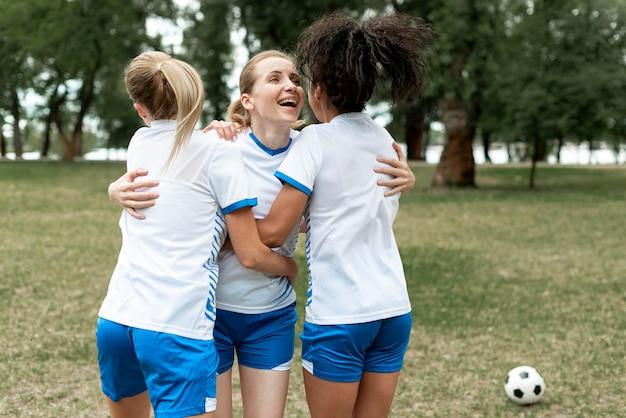 Vrouwen knuffelen op voetbalveld