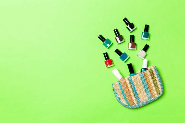 Vrouwen kosmetische zak met manicure en pedicure, heldere gelvernis op groene achtergrond met exemplaarruimte voor uw ontwerp en tekst. nagel werk plat lag concept