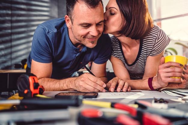 Vrouwen kussende echtgenoot tijdens keukenvernieuwing