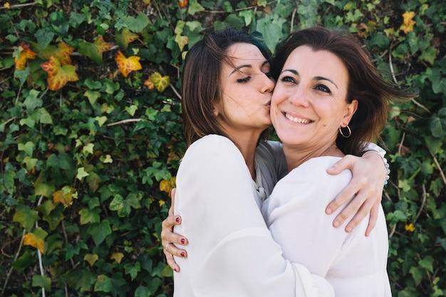 Vrouwen kussende vrouw in tuin