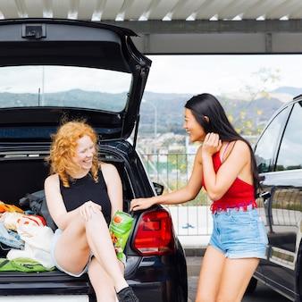 Vrouwen lachen en plezier hebben met de kofferbak van de auto