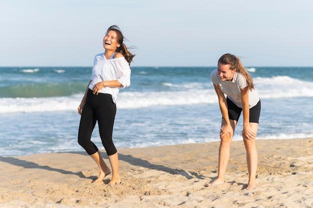 Vrouwen lachen op het strand tijdens het joggen