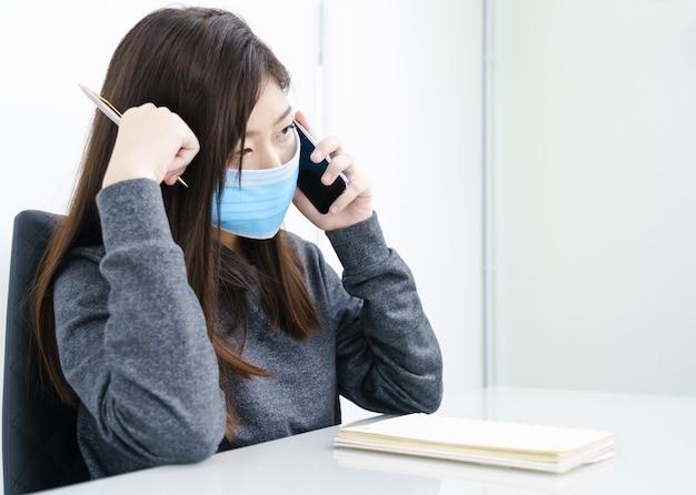 Vrouwen lang haar die beschermend masker dragen die en mobiele telefoon houden met behulp van