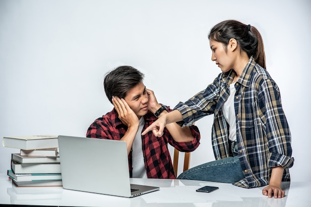 Vrouwen leren mannen op het werk met laptops te werken.