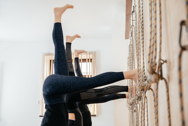 Vrouwen leren staan op handen in de buurt van muur in studio. ondersteboven yogapositie